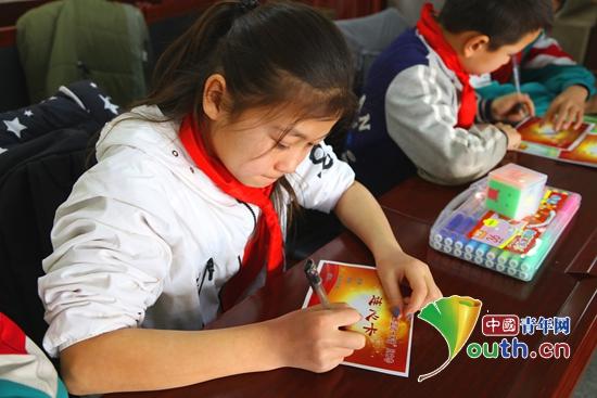 小朋友同写一张连心卡。吐鲁番市团委 供图