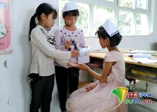 """图为田坝小学的""""小护士""""认真检查同学们的手是否干净。阚永志 供图"""