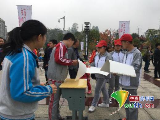 """岑巩县举行2018年""""思砚杯""""第三届千名青少年现场书画大赛。图为活动现场志愿者为参赛者发纸。"""
