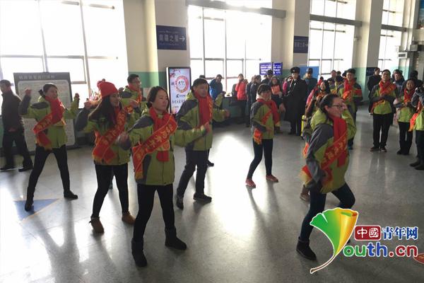 青年志愿者开展青果乐园快闪活动。 乌鲁木齐铁路局团委供图   中国青年网北京1月25日电(通讯员李红红)春运旅途别徘徊,快到青果乐园来,你的难处青果来分担1月24日上午,在人头攒动的乌鲁木齐南站候车厅里,伴随着欢快动人的志愿者快闪活动,乌鲁木齐铁路局团委2016年春运志愿者活动正式拉开帷幕,志愿者朝气蓬勃的精神风貌和立志服务旅客的嘹亮口号,立刻受到了在场旅客的围观和点赞,不少旅客纷纷拿出手机,记录下这难忘的时刻。  春运志愿服务活动启动仪式。 乌鲁木齐铁路局团委供图   据悉,今年春运期间